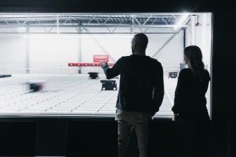 Personer i siluett ser utover robotlageret til New Wave