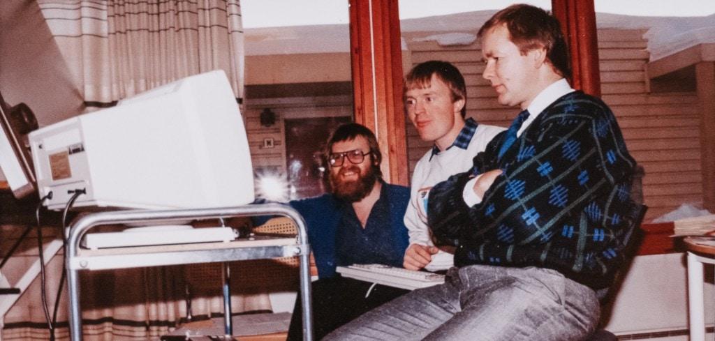 Bilde fra 80-tallet av tre menn foran en datamaskin
