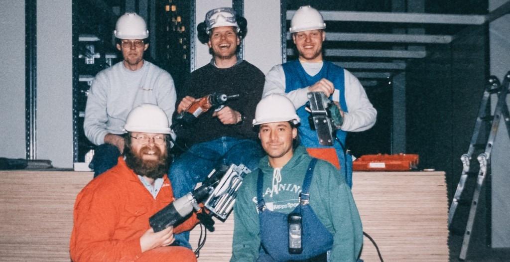 Fem menn fra 80-tallet med hjelm, verneutstyr og verktøy