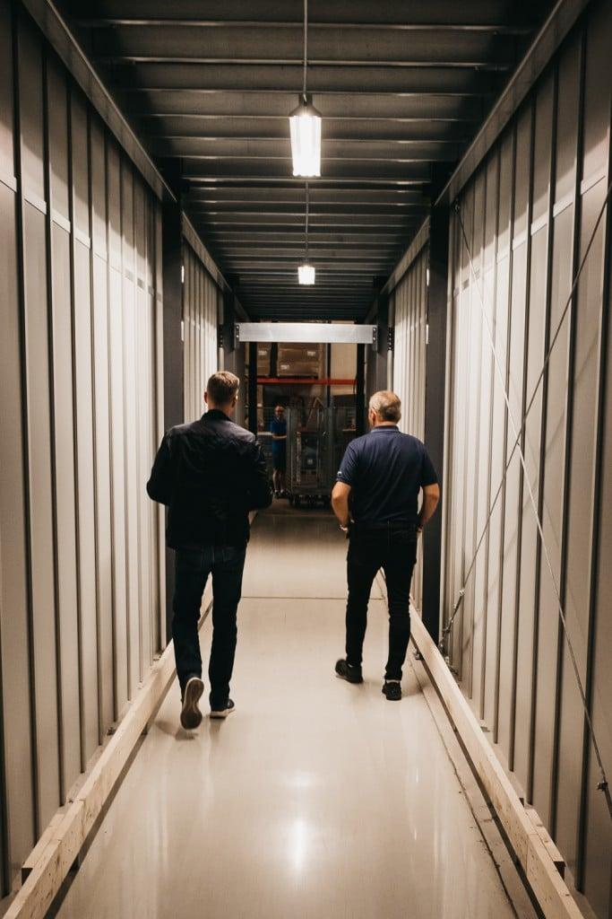 To menn går ned tilpasset tunnel gjennom AutoStore systemet til GS Bildeler i Oslo.