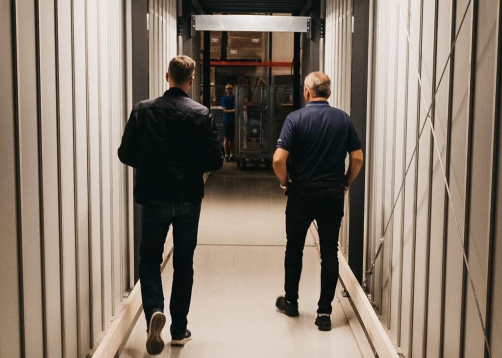 To menn går ned gjennom en spesiallagd tunnel i AutoStore-lageret til GS Bildeler