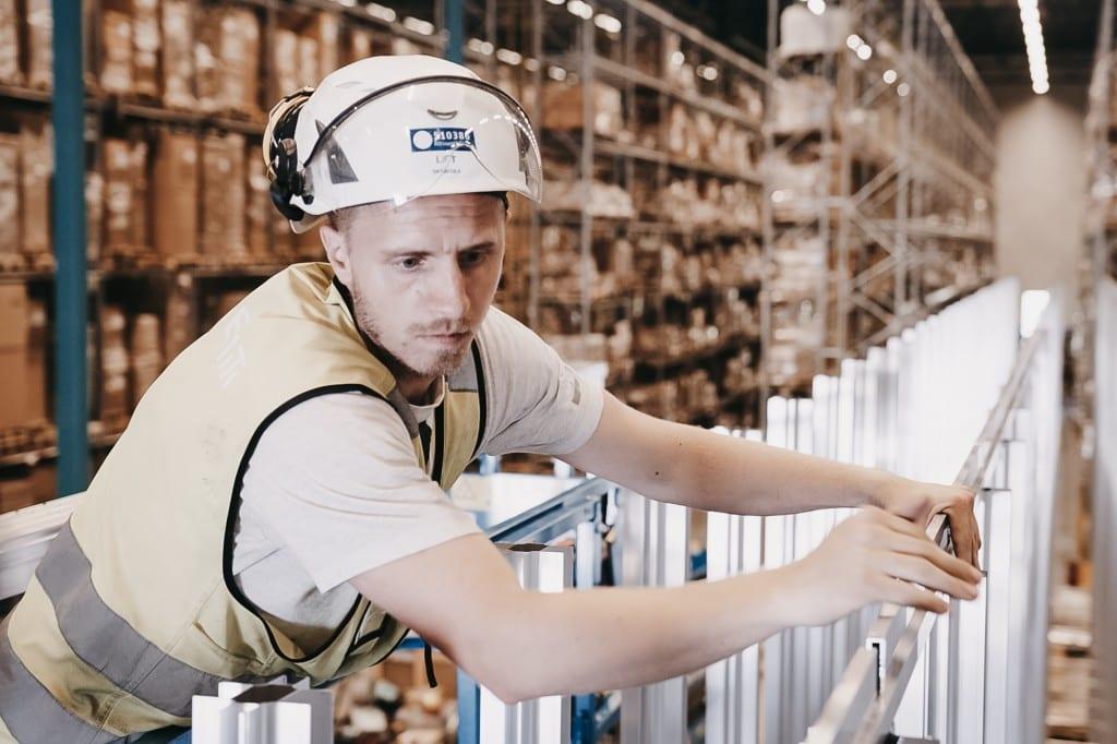 En mann I hjelm og gul vest bygger AutoStore-grid.