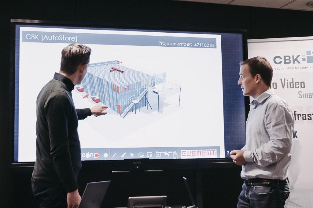 To menn peker og ser på en presentasjon med en tegning av en AutoStore-løsning.