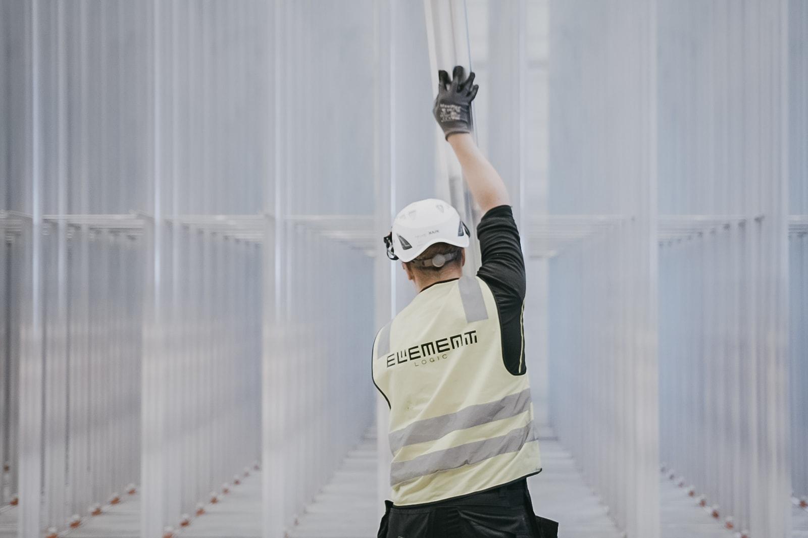 En mann med hjelm og gul vest bygger et AutoStore-grid bestående av aluminiumsøyler.