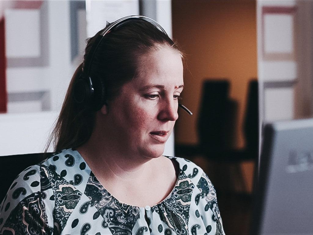 Et nærbilde av en kvinne som prater i hodetelefoner foran en dataskjerm.
