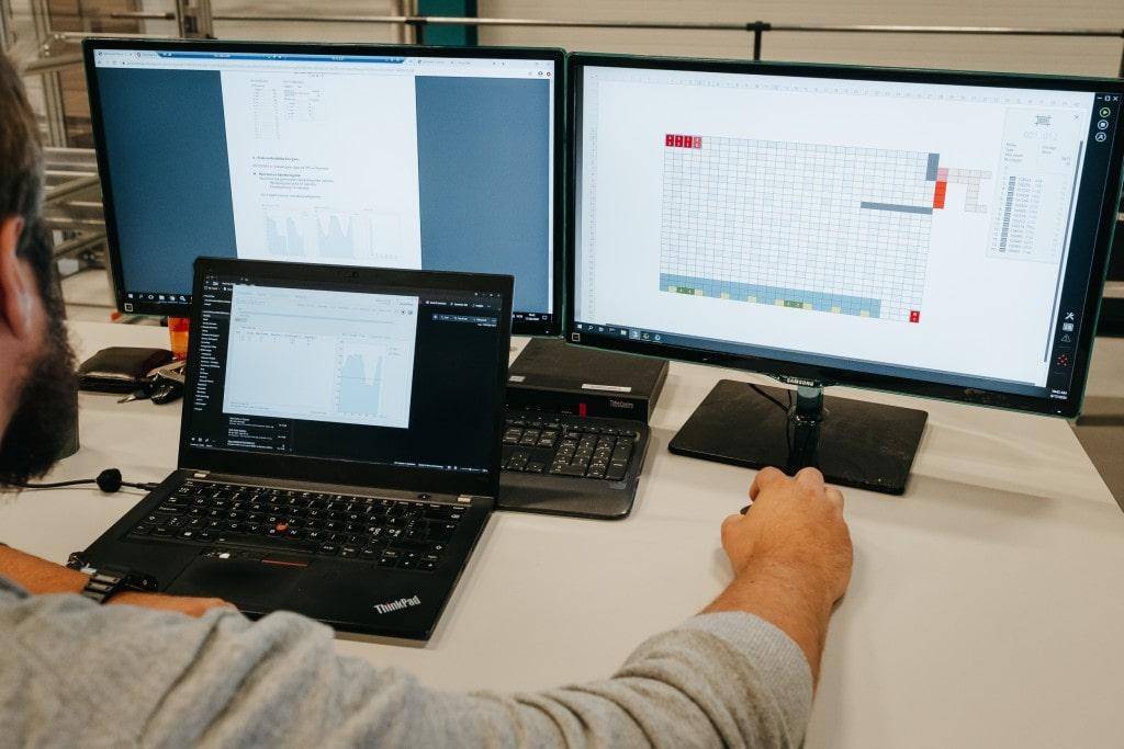 En mann jobber med en AutoStore-løsning med tre dataskjermer.