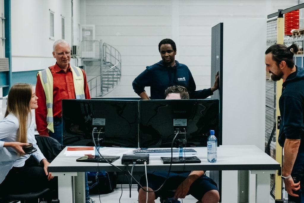 Fem personer jobber sammen foran en dataskjerm for å lære hvordan de drifter sitt nye AutoStore-system.