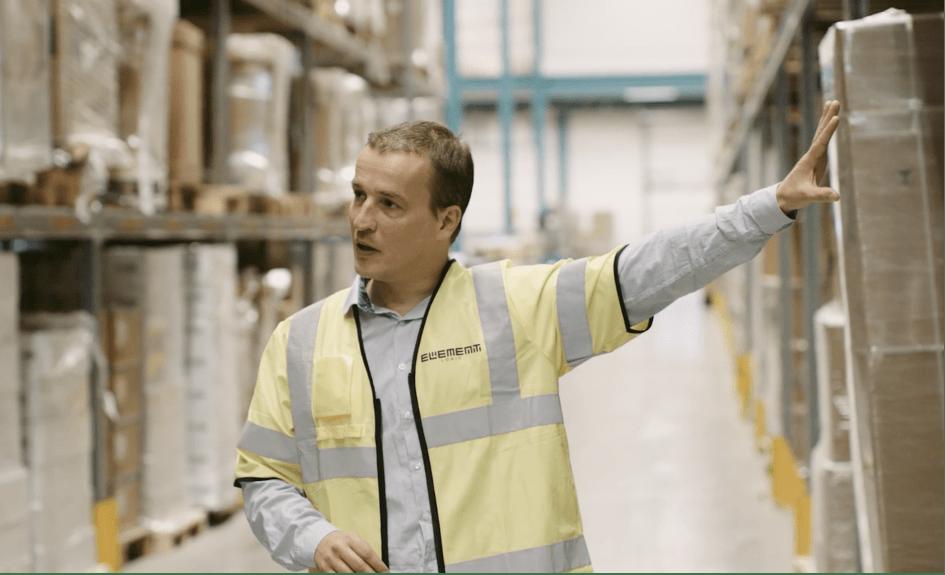 En mann i gul vest står i et varehus og ser på noe utenfor kameravidden