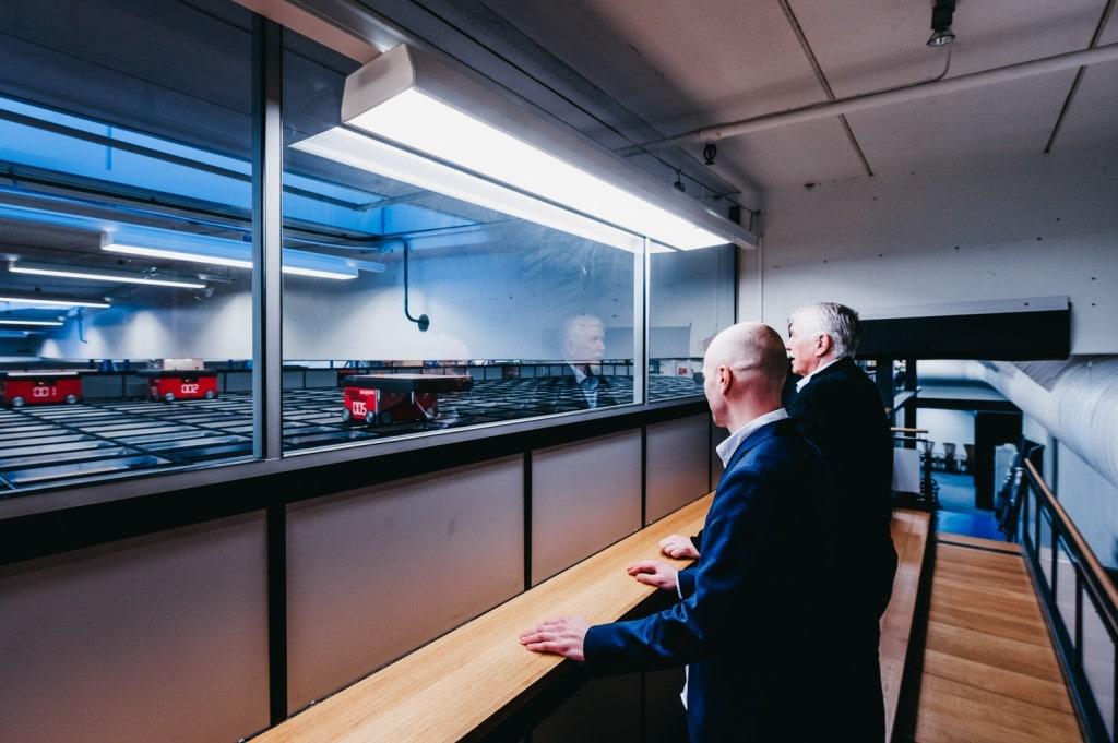 Jan Kleven og Roger Furnes ser utover AutoStore-systemet med AutoStore-roboter som jobber på griden.