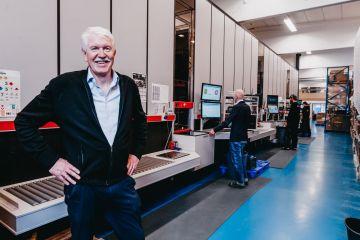 Daglig leder, Jan Kleven, smiler stolt til kamera foran Elotec sin AutoStore-løsning med ansatte som opererer portene i bakgrunnen.