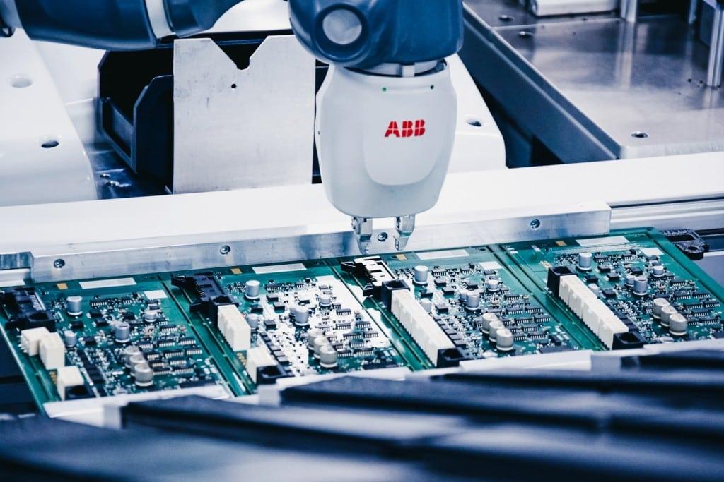 Et nærbilde av en automatisert robothånd som produserer elektriske komponenter.