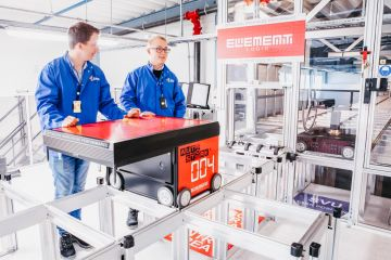 To menn i blå arbeidsdresser står bak en rød AutoStore-robot fra Element Logic.