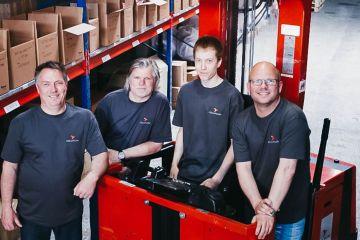 Fire Colliflow-ansatte står i lageret og smiler mot kamera.