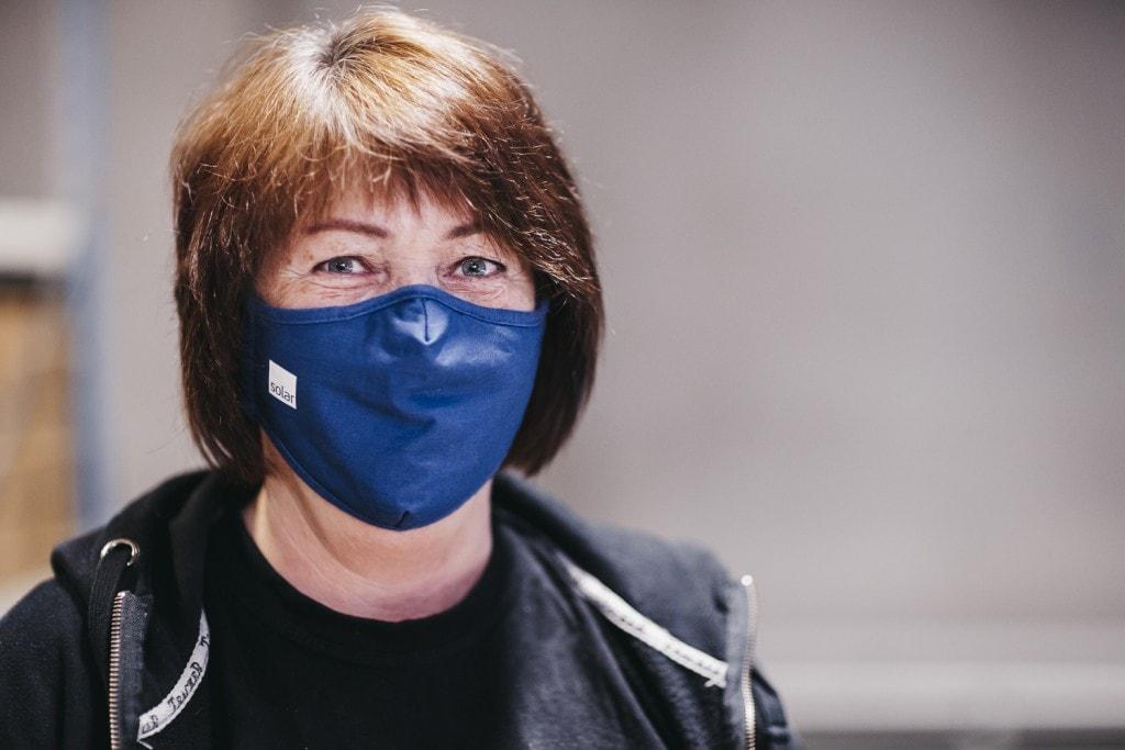 Kvinnelig lagermedarbeider med en ansiktsmaske.