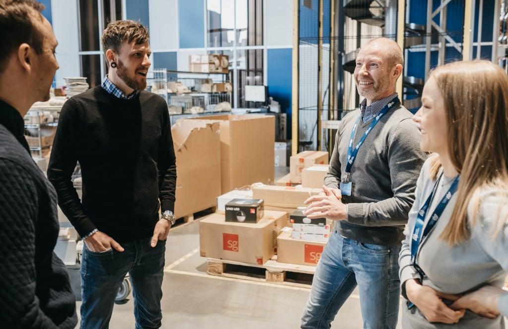 To ansatte i Element Logic prater med to smilende kunder i et lager.