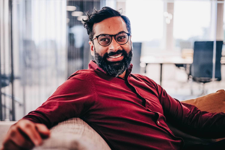 En smilende Khanani sitter på en sofa og ser i kamera.
